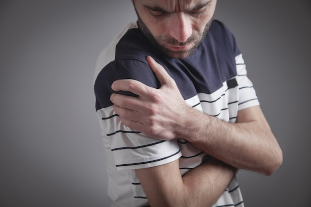 Caucasian young man with a pain in shoulder.