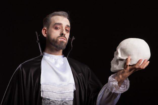 무서운 얼굴과 드라큘라 의상을 입고 카메라를 들여다보고 두개골을 들고 있는 백인 청년. 뱀파이어 눈을 가진 무섭고 위험한 남자.