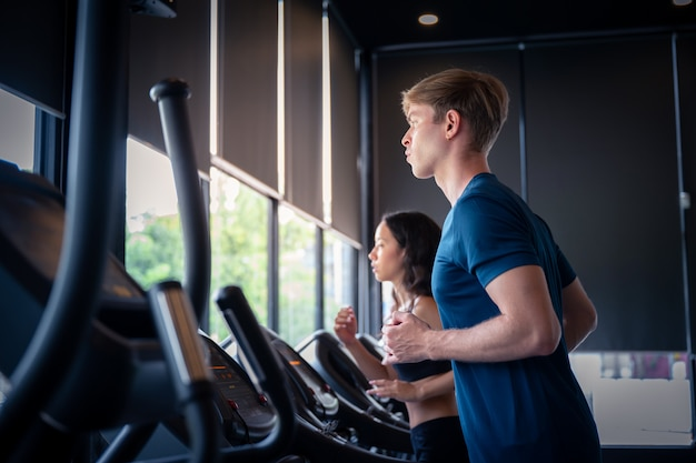 Caucasian young man and woman running on machine at gym