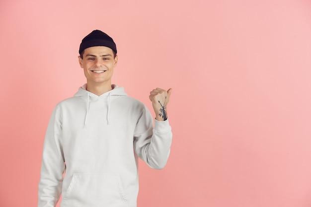 Кавказский молодой человек современный портрет на фоне розовой студии