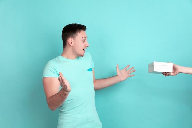 Портрет кавказского молодого человека на синей стене