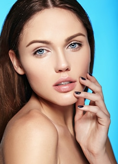 Caucasian young model with nude makeup touching her perfect clean skin on blue