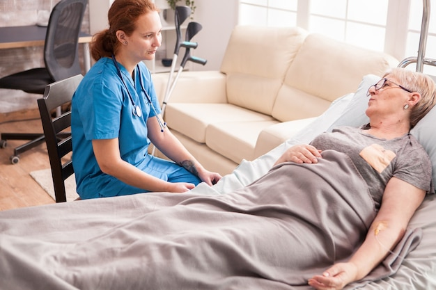 Caucasian young nurse supporting senior woman in nursing home lying in bed.