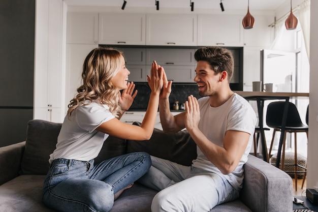 スタイリッシュなフラットでポーズをとる白人の若者。ソファで笑っているのんきなカップルの屋内肖像画。