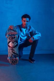 Кавказский молодой скейтбордист позирует на темном фоне неоновой подсветки