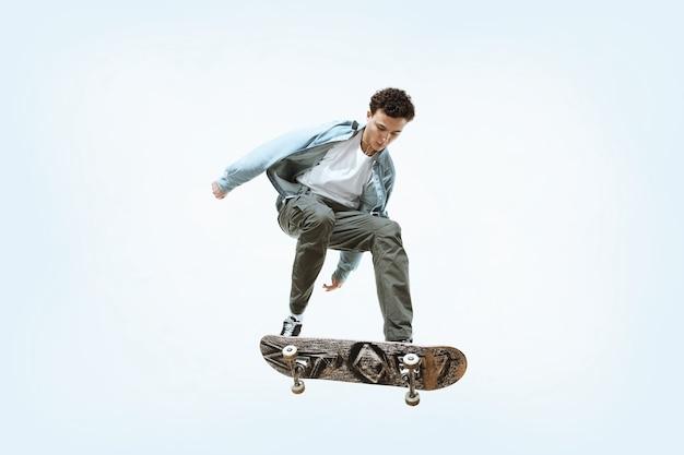 白い背景で隔離に乗って白人の若いスケートボーダー