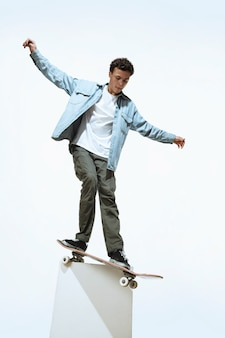 Caucasian young skateboarder riding isolated on a white background