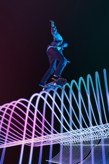 Кавказский молодой скейтбордист катается на темном неоновом фоне линии