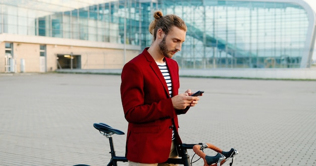 Caucasian young smiled handsome man standing at bicycle and texting message on smartphone. stylish guy in red jacket leaning on bike and tapping or scrolling on mobile phone at aeroport. outdoor.