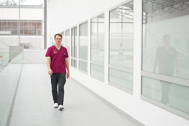 Кавказский молодой улыбающийся веселый доктор имеет прогулку в коридорах клиники. человек на работе.