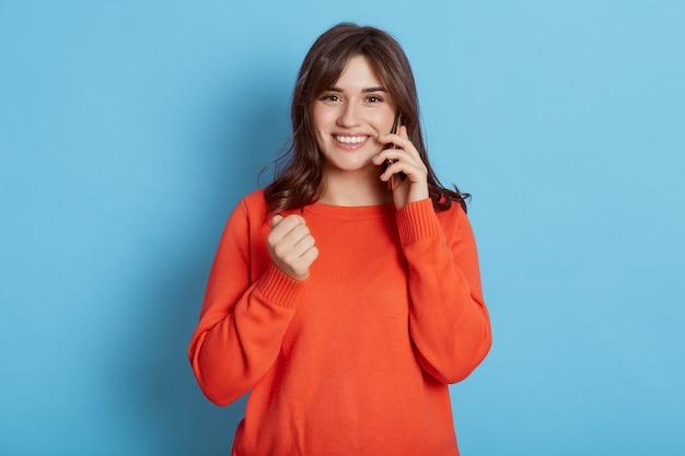 電話で話し、誰かと良いニュースを共有する白人の若い笑顔の女性