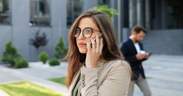 通りで携帯電話で話している眼鏡の白人の若いスタイリッシュな実業家。屋外で携帯電話で話す美しい女性。電話をかけている眼鏡の魅力的な女性。会話。