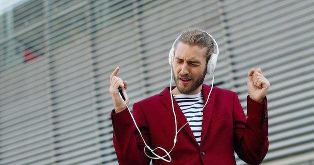 スマートフォンで音楽を聴いて歌うヘッドフォンで白人の若いスタイリッシュなハンサムな男。屋外。赤いジャケットを着た陽気な格好良い面白い男が歌って歌を聴きます。携帯電話プレーヤー。
