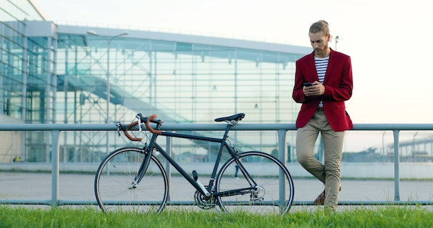 Caucasian young stylish handsome man standing at street with bike. looking at hand watch and texting message on smartphone. male tapping and scrolling on mobile phone with bicycle outside. waiting.