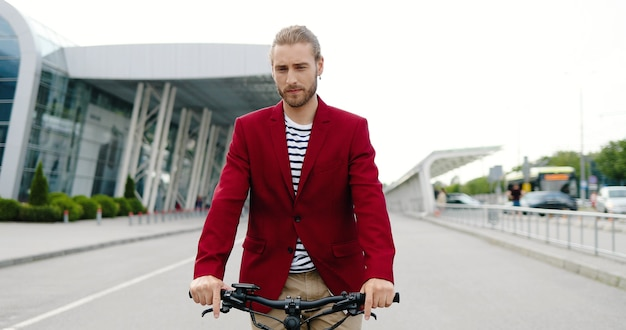 Caucasian young stylish man in red jacket riding electric scooter and looking for time at hand watch. outdoor. handsome guy driving and rushing in city. being late concept.