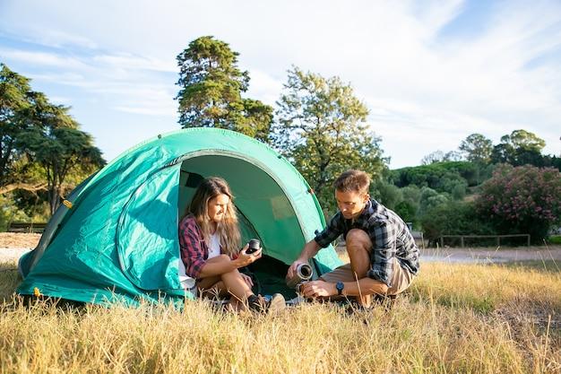 芝生の上でキャンプし、テントに座っている白人の若い観光客。魔法瓶からお茶を飲み、一緒に自然でリラックスして幸せなカップル。観光、冒険、夏休みのコンセプトをバックパッキング