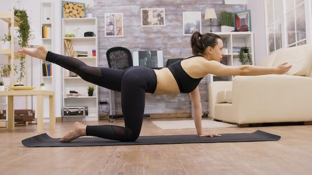 居間で腰痛の運動をしている白人の若い女性。