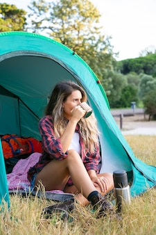 お茶を飲み、テントに座って目をそらしている白人の若い女性。公園の芝生でキャンプし、風景を見ている思いやりのある女性旅行者。観光、冒険、休暇のコンセプトをバックパッキング