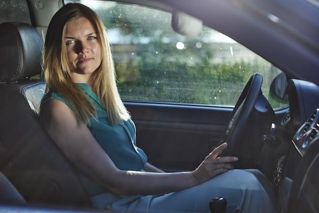 白人の若い女性は夏の日に車を運転します