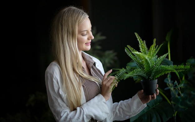 집에서 녹색 잎 식물을 들고 백인 젊은 여자. 가정 정원 가꾸기.