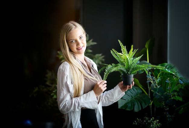 집에서 녹색 잎이 있는 식물을 들고 있는 백인 젊은 여성 홈 원예