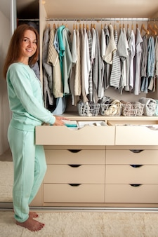 Caucasian young woman housewife holding container with socks, panties and underwear. clothes storage.