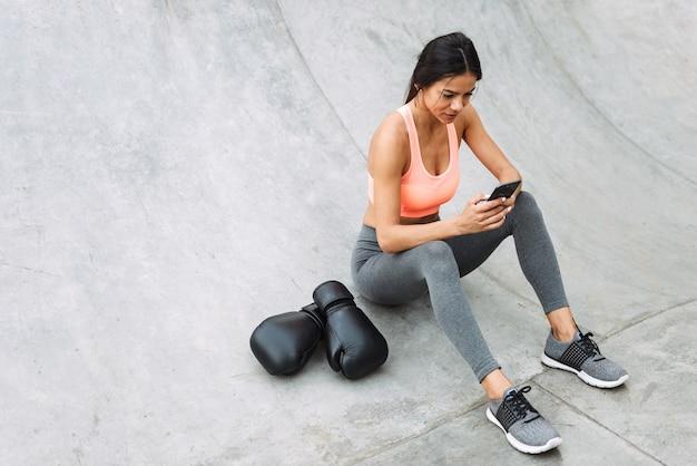 권투 장갑과 콘크리트 바닥에 앉아있는 동안 핸드폰을 들고 운동복에 백인 젊은 여자