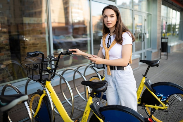 Caucasian young woman pays for bike rental in app