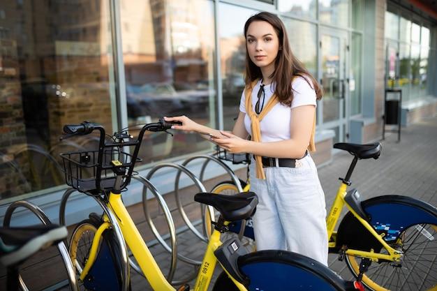 白人の若い女性がアプリで自転車のレンタル料金を支払う