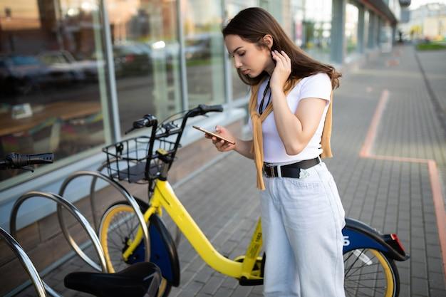 백인 젊은 여성이 앱에서 자전거 대여 비용을 지불합니다.