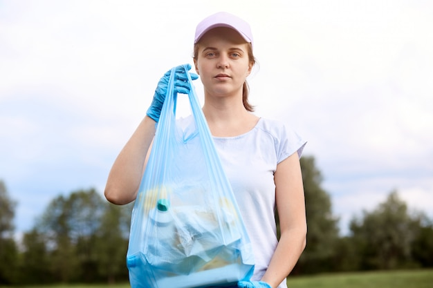 Caucasian young woman picking up trash from meadow. female cleaning field, collecting litter in garbage bag, wearing t shirt and base ball cap, standing with trees and sky i