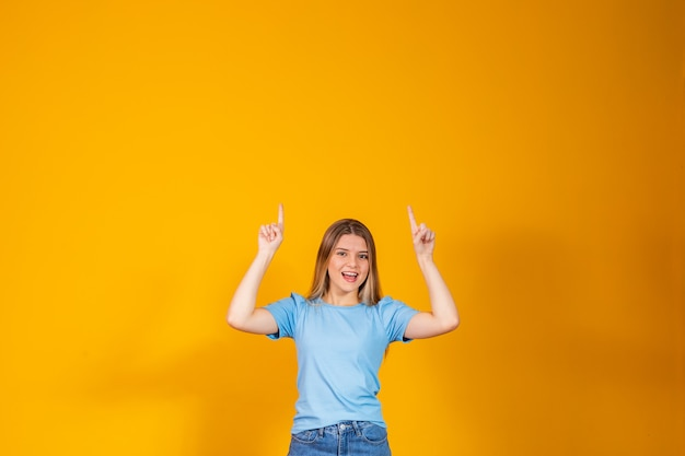 Caucasian young woman pointing up with free space for text.