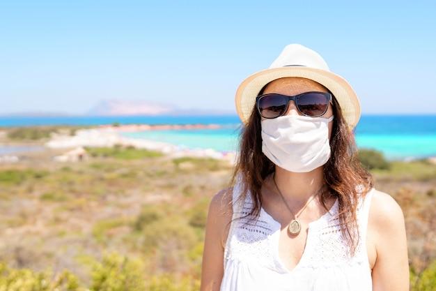 白人の若い女性が明るい色の熱帯の海で夏休みにコロナウイルス保護マスクで写真のポーズ