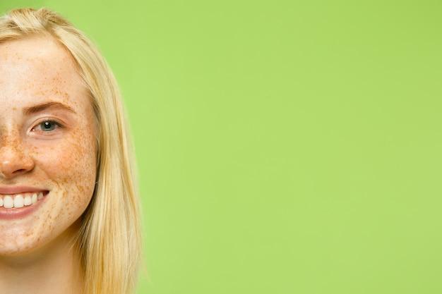 Ritratto alto vicino della giovane donna caucasica sulla parete verde. modello femminile in camicia gialla con capelli biondi e lentiggini. concetto di emozioni umane, espressione facciale.