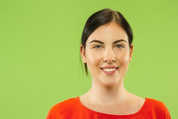 백인 젊은 여자의 녹색 공간에 초상화를 닫습니다. 웃 고 행복해 보이는 빨간 셔츠에 갈색 머리 여성 모델