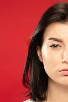 Ritratto alto vicino della giovane donna caucasica su studio rosso