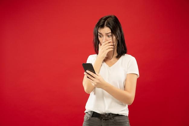 Поясный портрет кавказской молодой женщины на фоне красной студии. красивая женская модель в белой рубашке. понятие о человеческих эмоциях, выражении лица. покупает онлайн, оплата счета, выглядит шокированным.