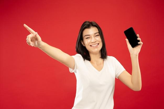 赤いスタジオの背景に白人の若い女性の半身像。白いシャツの美しい女性モデル。人間の感情、表情、販売の概念。電話で指さして、幸せそうに見えます。