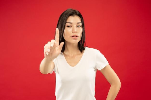 赤いスタジオで白人の若い女性の半身像