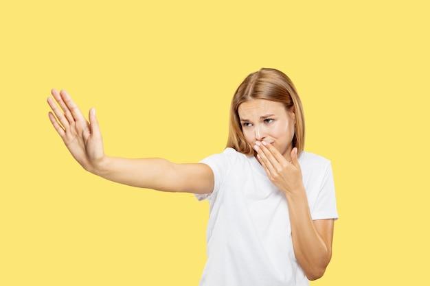 노란색 스튜디오 배경에 백인 젊은 여자의 절반 길이 초상화. 흰 셔츠에 아름 다운 여성 모델입니다. 인간의 감정, 표정의 개념. 역겹고 화난 것 같고 얼굴을 가린다.