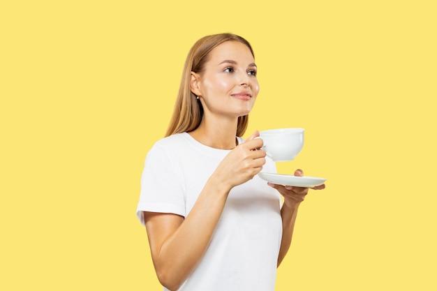 黄色のスタジオの背景に白人の若い女性の半身像。白いシャツの美しい女性モデル。人間の感情、表情、販売の概念。カップでコーヒーやお茶を楽しめます。