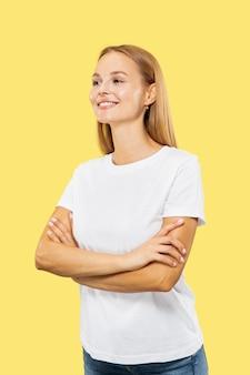노란색 스튜디오 배경에 백인 젊은 여자의 절반 길이 초상화. 흰 셔츠에 아름 다운 여성 모델입니다. 인간의 감정, 표정, 판매의 개념. 서있는 손은 자신감을 가지고 교차했습니다.