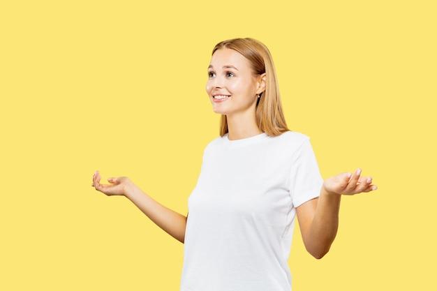 노란색 스튜디오 배경에 백인 젊은 여자의 절반 길이 초상화. 흰 셔츠에 아름 다운 여성 모델입니다. 인간의 감정, 표정의 개념. 빈 막대를 표시하고 웃고 있습니다.
