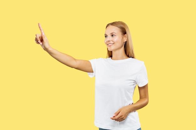 Поясной портрет кавказской молодой женщины на желтом фоне студии. красивая женская модель в белой рубашке. понятие о человеческих эмоциях, выражении лица. прикосновение к пустой строке поиска и улыбка.