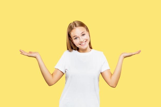 노란색 스튜디오 배경에 백인 젊은 여자의 절반 길이 초상화. 흰 셔츠에 아름다운 여성 모델
