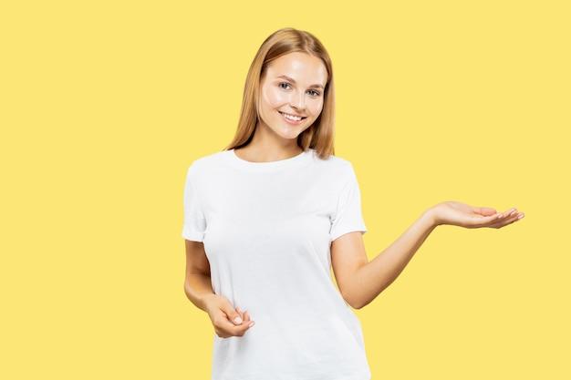 黄色のスタジオの背景に白人の若い女性の半身像。白いシャツの美しい女性モデル