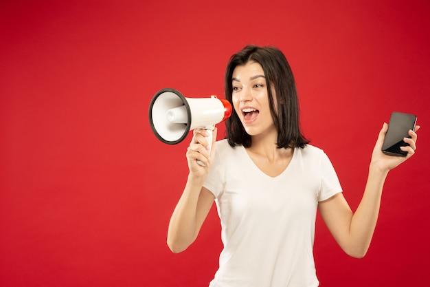 Ritratto a mezzo busto della giovane donna caucasica su sfondo rosso studio. bello modello femminile in camicia. concetto di emozioni umane, espressione facciale, vendite. tenendo il telefono e chiamando a bocca aperta.