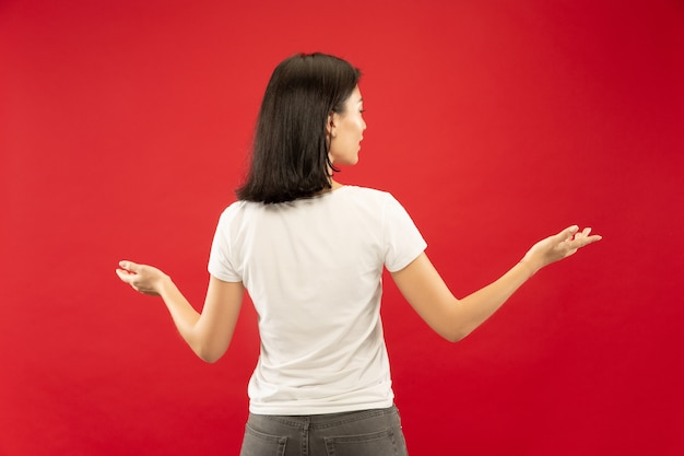Caucasian young woman's half-length portrait on red studio background. beautiful female model in white shirt. concept of human emotions, facial expression. showing and pointing something.