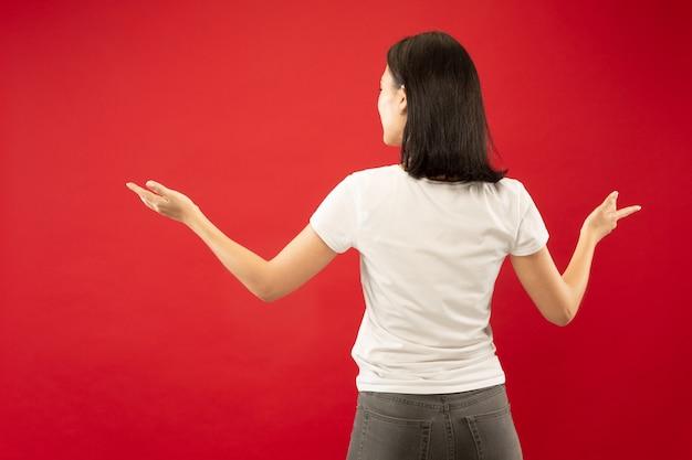Ritratto a mezzo busto della giovane donna caucasica su sfondo rosso studio. bello modello femminile in camicia bianca. concetto di emozioni umane, espressione facciale. mostrare e indicare qualcosa.