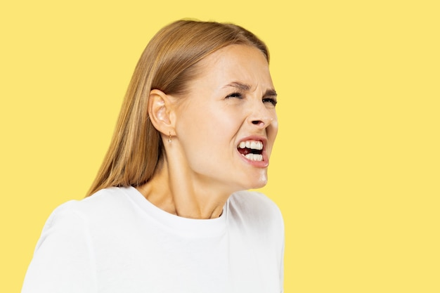 Ritratto a mezzo busto della giovane donna caucasica su sfondo giallo studio. bello modello femminile in camicia bianca. concetto di emozioni umane, espressione facciale, vendite. urla arrabbiata, sconvolta, aggressiva.